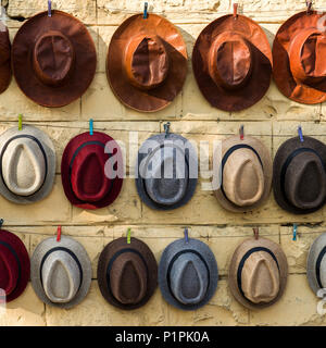 Various styles of hats hanging on display in a row on a wall; Jaisalmer, Rajasthan, India - Stock Image