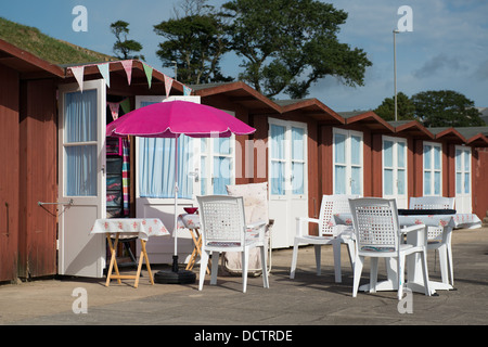 Beach hut with tables, chairs and umbrella set out on a summers day in Swanage, Dorset - Stock Image
