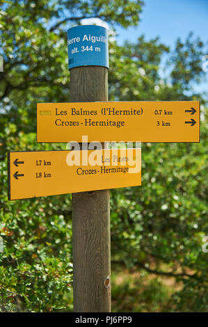 Yellow fingerpost signs on a timber post on the hillside above Tain L'Hermitage in the Drome department, Rhone Alps region, France - Stock Image