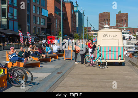 Oslo Aker Brygge, view of people relaxing on a summer afternoon on the Stranden - a waterfront promenade in the Aker Brygge harbour area of Oslo. - Stock Image