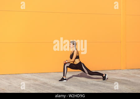 Young attractive sporty woman wearing black sporwear practicing sport exercises in morning on street, stretching legs and standing on ashtanga pose, o - Stock Image