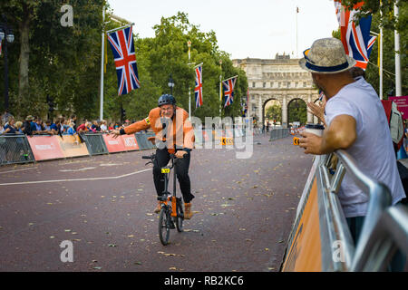 A man waving as he rides along The Mall with onlooking crowd, Brompton World Championships 2018, London, UK - Stock Image