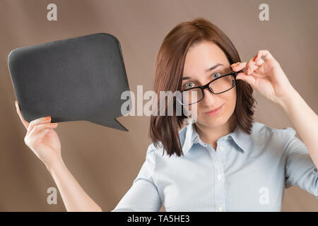 Woman in glasses holding blank black slate with copy space. Short message, question and announcement theme. - Stock Image