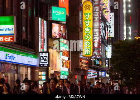 Detail of neon signs in the Susukino area at night in Sapporo, Hokkaido, Japan, with crowd of pedestrians at the dark bottom of the image. - Stock Image