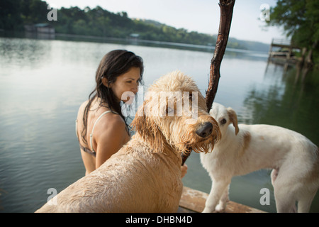 A woman swimming with her two dogs in a lake. - Stock Image