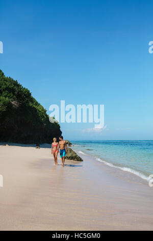 Shot of young man and woman walking on the tropical coast. Young couple strolling on the beach, enjoying summer - Stock Image