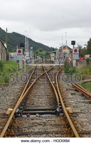 An end on view of Porthmadog mainline railway station and level crossing taken from a position further up the line. - Stock Image