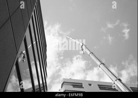 Crane reflected in front of building in Tokyo - Stock Image