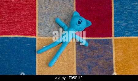 Knitted toy of a bear on a multi coloured squared rug. - Stock Image