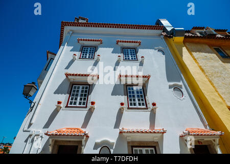 Whitewashed facade of house with brown flower pots in Cascais, Portugal. - Stock Image