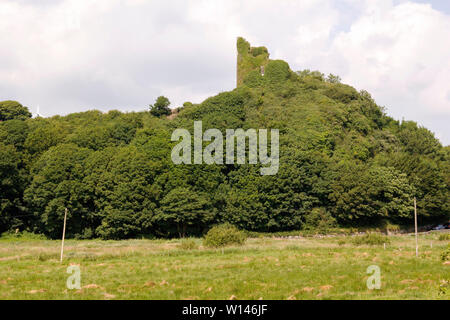 Remains of Dunhill Castle visible on a rocky hill overlooking Anne Stream Valley in County Waterford,Ireland. - Stock Image