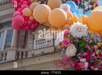 Brook Street London W1 street sign on wall surrounded by colourful balloons and silk flowers - Stock Image