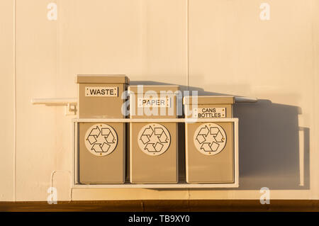 Three tidy waste and recycling receptacles hung on painted white metal exterior wall of cruise ship. - Stock Image