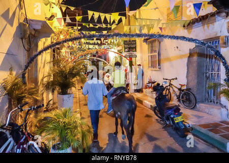 Cartagena Colombia Old Walled City Center centre Getsemani night nightlife Hispanic resident residents decorated street paper banners man boy riding m - Stock Image