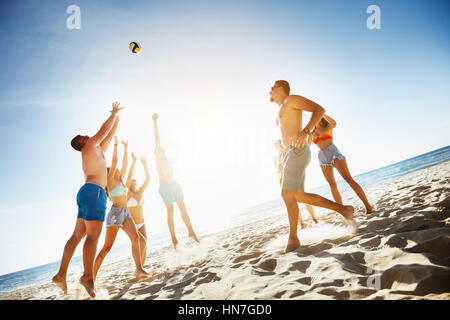 Group friends plays ball beach sea - Stock Image