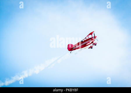 Red airplane with propellers and white smoke on the tail flying in the blue sky - Stock Image