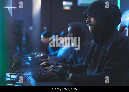 Group of serious gloomy young hackers in hoodies sitting in row and typing on keyboards fastly in server room - Stock Image