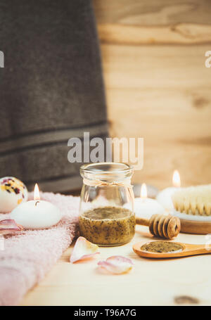 Selective focus on sauna honey scrub. Scrubbing honey and coffee mixture on body in hot sauna helps open the pores and renew, rejuvenate the skin on b - Stock Image