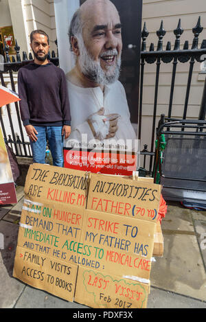 London, UK. 10th August 2018. Ali Mushaima who has been on hunger strike at the Bahrain embassy since the start of August to save his fathers life stands in front of a banner with a photograph of his father and a poster about his father and his hunger strike. A vigil by Inminds Islamic human rights organisation vigil calling for the immediate release of Hassan Mushaima and all the other 5000 Bahraini prisoners of conscience languishing in the Al-Khalifa regimes jails. Credit: Peter Marshall/Alamy Live News - Stock Image