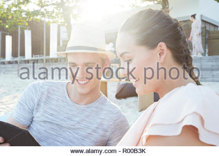 Young couple smiling on beach - Stock Image