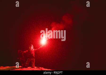 Snowboarder with signal fire in hands stands at night snowfall - Stock Image