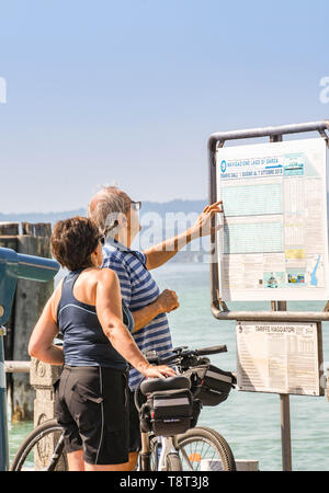 SIRMIONE, LAKE GARDA, ITALY - SEPTEMBER 2018: Man and woman checking the ferry timetable at the harbour in Sirmione on Lake Garda. - Stock Image