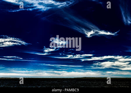 A Vibrant and vivid sky cloudscape with white coloured wispy Cirrus clouds in a dark blue sky. Beauty in nature. New South Wales, Australia. - Stock Image