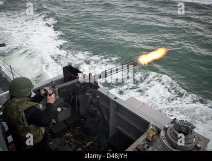 SS Monsoon fires a .50 caliber machine. - Stock Image