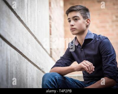 Boy, teenager, 14 years, sitting on a staircase, view into the future, Portrait, Germany - Stock Image