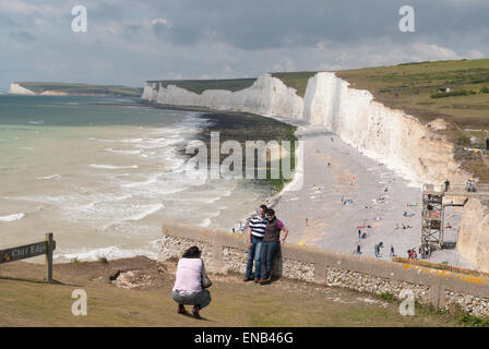 Two people have their picture taken at Birling Gap East Sussex UK - Stock Image