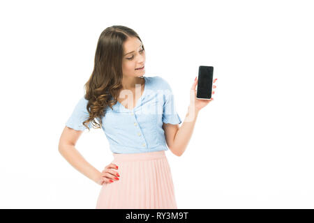 smiling beautiful girl showing smartphone with blank screen isolated on white - Stock Image