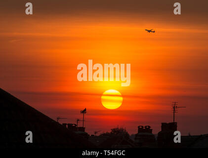 London, UK. 20th April, 2019. Aircraft takes off from Heathrow as the sun sets over suburban rooftops in a clear orange sky after a day of cloudless skies and soaring summer temperatures during Easter holiday weekend. Credit: Malcolm Park/Alamy Live News. - Stock Image