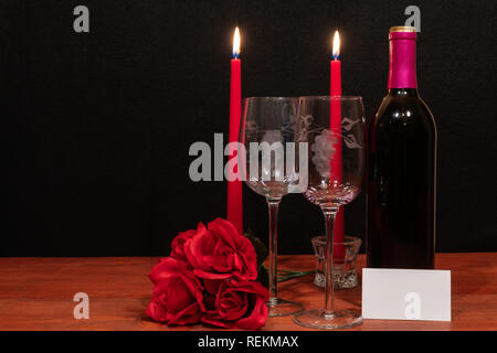 Beautiful etched wine glasses and bottle of red wine, red candles and red roses on wooden table with name tag on dark background. Valentines, Mothers  - Stock Image