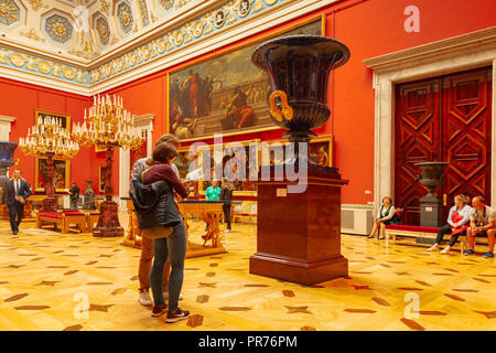 19 September 2018: St Petersburg, Russia - Young couple studying a guide book while standing near a large urn in the Hall of Italian Paintings, Hermit - Stock Image