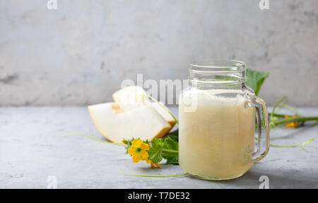smoothie melon in mason jar, melon pieces on gray background - Stock Image