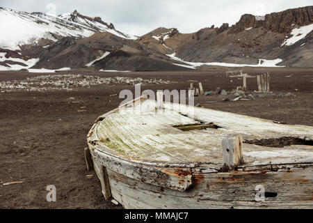 A decaying water boat, used for storing fresh water, lies abandoned on the beach on Deception Island - Stock Image
