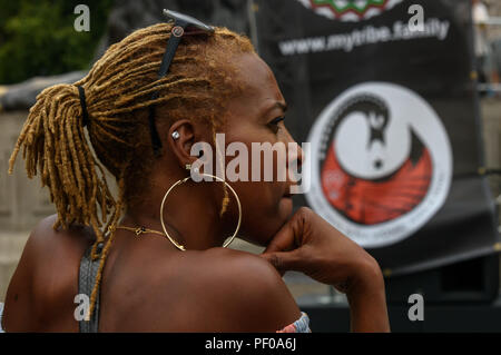 London, UK. 18th August 2018. A woman listens at the annual National Memorial event in Trafalgar Square remembers and honours the victims of the African Holocaust/Transatlantic Slave Trade and promoted International Slavery Remembrance Day, 23rd August. The event called for Africans to celebrate their identity and to remember their ancestors, and began with libations remembering many black heroes. ers talked about the discrimination in the UK educati Credit: Peter Marshall/Alamy Live News - Stock Image