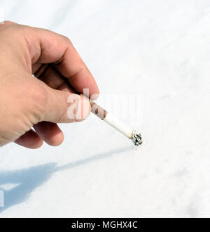 Single male hand stubbing out a smoked cigarette butt into a snow background with copy space area for nicotine addiction and smoking related health de - Stock Image