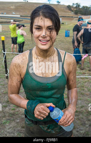 A smiling fit healthy young 19 year old woman competitor in an 8km obstacle course challenge - Stock Image