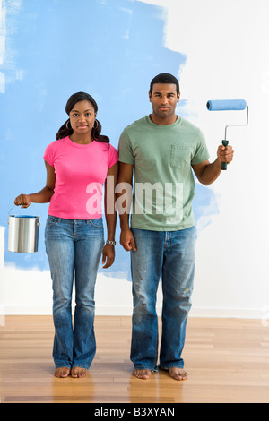 African American couple next to half painted wall with paint supplies American Gothic style - Stock Image