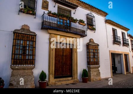 RONDA, ANDALUSIA / SPAIN - OCTOBER 08 2017: WHITE HOUSE WITH METAL BALCONY AND WOODEN DOOR - Stock Image