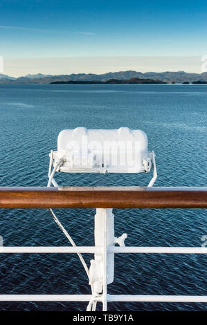 White metal marine exterior light fixture on railing of cruise ship, early morning, Alaska Inside Passage route. - Stock Image