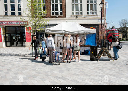 People queuing to buy bread in front of Celtic Bakers stall on Navigator Square Archway N19 formally Archway Roundabout - Stock Image