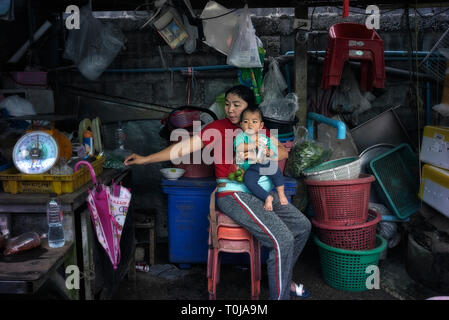 Working mother holding onto her child whilst managing her back street market stall. Thailand Southeast Asia - Stock Image