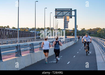 People exercising on the Iron Cove Bridge that joins the Sydney suburbs of Drummoyne and Rozelle over the upper reaches of Sydney harbour. - Stock Image