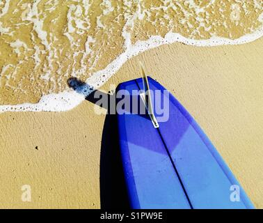 A surfboard at the waters edge at the beach. Malibu, California USA. - Stock Image