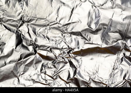 Crumpled Aluminum tin foil texture with light reflections on the shiny metallic silver wrapping - Stock Image