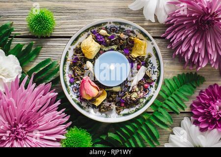Decorative Plate with Blue Candle, Dried Herbs, Dried Flowers and Spring Flowers - Stock Image