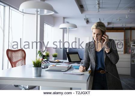 Female interior designer talking on smart phone in office - Stock Image