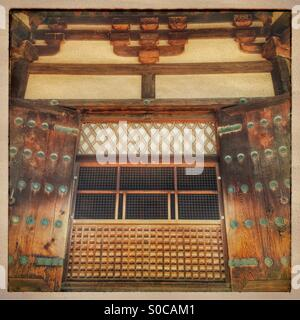 Ancient wooden Japanese window with shutters, decorative lattice  pattern and brass studs. Vintage frame and sandstone - Stock Image